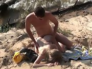 Bare couple has sex on the beach while waves lap at their feet